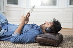 Asian man lying on the floor reading his tablet PC. Royalty Free Stock Photography
