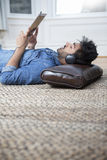 Asian man lying on the floor reading his tablet PC. Stock Photos