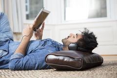 Asian man lying on the floor reading his tablet PC. Stock Images