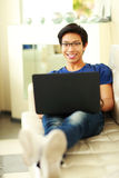 Asian man lying on the sofa with laptop Royalty Free Stock Image