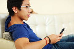 Asian man lying on the sofa Royalty Free Stock Images