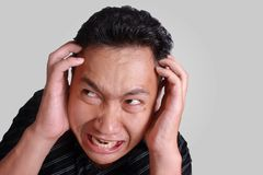 Asian Man Mad Angry Stressed Expression. Headshot portrait of funny young Asian man angry stressed furious expression, isolated on grey Royalty Free Stock Photography