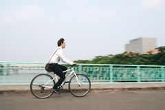 Profile image of an active businessman riding a bicycle on the w. Asian man mad riding bicycle in urban city commuting with speed and hipster trendy Royalty Free Stock Image