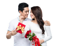 Asian man makes present to his lovely sweetheart. Young man giving a gift. Stock Image