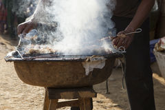 Asian man making barbecue in traditional way Stock Photo