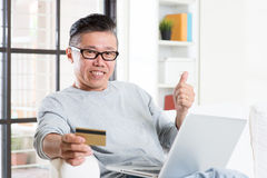Asian man making online payment and thumb up Royalty Free Stock Images