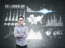 Asian man and many graphs on blackboard. Portrait of a cheerful Asian businessman standing near a blackboard with many graphs drawn on it.  Elements of this Stock Images
