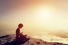 Asian man meditates in yoga position. Above clouds. Asian man meditates in yoga position in high mountains above clouds at sunset. Unique concept of meditation Stock Illustration