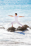 Asian man meditates in yoga position on high Stock Photo