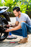 Asian man at motorcycle maintenance Stock Photo