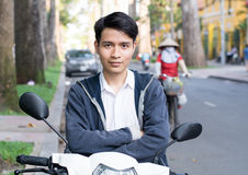 Asian man with a motorcycle on the street Royalty Free Stock Photography