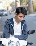 Asian man with a motorcycle on the street Stock Photo