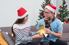 Asian man open gold gift box with girlfriend on sofa at Christmas party,holiday celebration.surprise concept stock photo