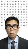 Asian man overwhelmed by social media symbols Royalty Free Stock Photography