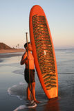 Asian Man with Paddleboard. An Asian man holding his paddleboard looks inot the ocean stock photography