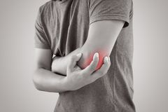 Asian man with pain in elbow against gray background. People suffering from chronic joint rheumatism. Body & Health concept Stock Photo