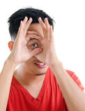Asian man peeping through fingers hole Royalty Free Stock Images