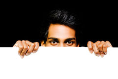 Asian man peeping over placard Stock Photo