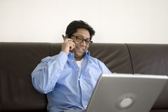 Asian man on phone with laptop. Relaxed asian man speaking on the phone working on a laptop Royalty Free Stock Images