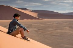 Asian man photographer sitting on sand dune. Young Asian man traveler and photographer looking at scenery while sitting on sand dune in Namib desert of Namibia Royalty Free Stock Image