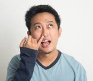 Asian man picking nose. Disgusting Asian man picking nose with eyes looking up, on plain background Stock Image