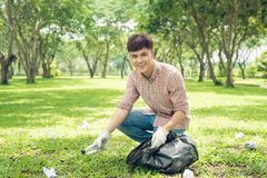 Asian man picking up plastic household waste in park.  Stock Photo
