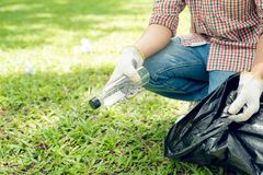 Asian man picking up plastic household waste in park.  royalty free stock image