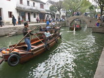 Asian Man Pilots Boat in Water Town. An Asian man drives a boat under a bridge in an ancient water town in China royalty free stock photo