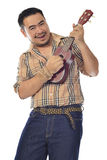 Asian man in plaid playing Ukulele Royalty Free Stock Photos