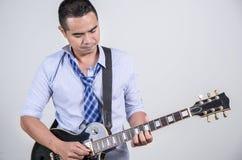 Asian man playing guitar. Asian man playing electric guitar royalty free stock images