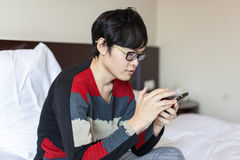 Asian man playing phone on bed Royalty Free Stock Photo