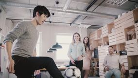 Asian man plays with football in office during break. Happy friends stand in circle, hold physical activity slow motion. stock footage