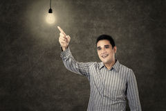 Asian man pointing a lit light bulb Royalty Free Stock Photo