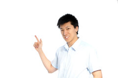 Asian man pointing to blank copyspace. Smiling young Asian man facing the camera and pointing to the left of the frame with his finger to blank white copyspace Royalty Free Stock Image