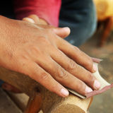 Asian man polishing sandpaper wood sculpture Stock Image