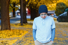 Asian man in a Polo T-shirt walks in a street Royalty Free Stock Photo