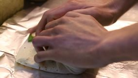 Preparing Mexican food, making burritos in the kitchen of Mexican restaurant. An Asian man preparing Mexican food, making delicious burritos in the kitchen of a stock footage