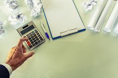Asian man pressing calculator for business finance on desk office white royalty free stock image