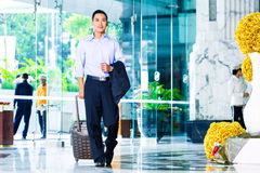 Asian man pulling suitcase in hotel Royalty Free Stock Image