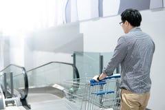 Asian man pushing shopping cart on travelator. Young Asian man shopper pushing shopping cart trolley on travelator escalator in supermarket or grocery store Royalty Free Stock Photos