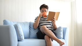 Asian man reading book and drinking coffee on sofa at home.  stock video footage