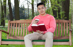 Asian man reading book in garden Stock Image