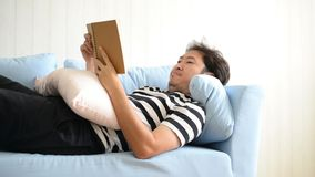 Asian man reading book lying on the sofa.  stock footage