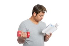 Asian man reading a book with red dumbbell royalty free stock photo