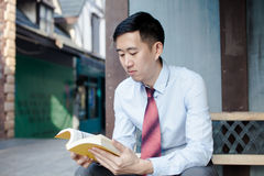 Asian Man Reading a Book Sitting on Bench Royalty Free Stock Image