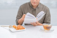 Asian man reading a book during tea break in the morning stock photo