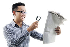 Asian man reading newspaper with magnifier. Excited Asian man reading newspaper with magnifier glass, isolated on white background stock image