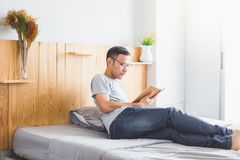 Reading book. Asian man reading a novel in his bedroom Royalty Free Stock Photos