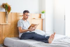 Reading book. Asian man reading a novel in his bedroom Royalty Free Stock Images