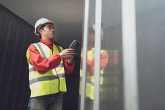 Asian man reefer technician is seriously working and monitoring reefer container at the port. Engineer checking equipment stock photography